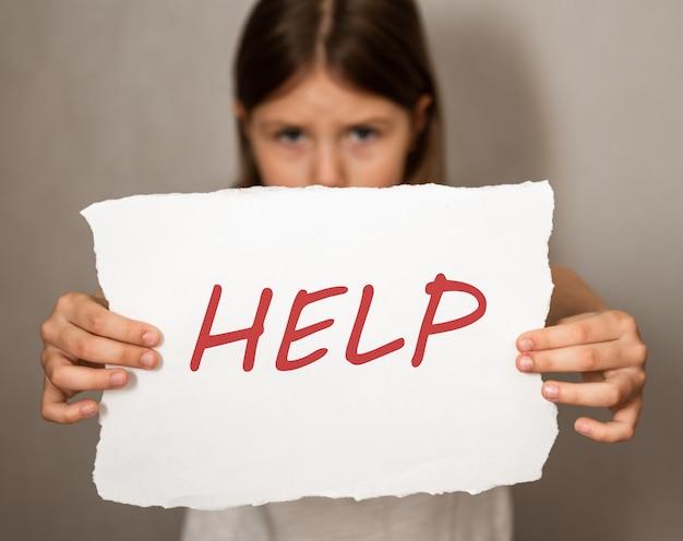 ヘルプサインを持って立っている悲しい落胆した少女
