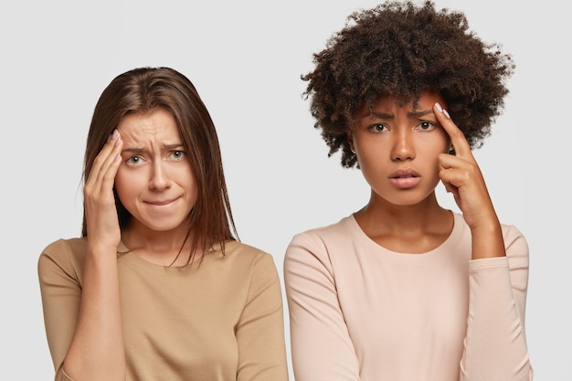 悲しい落胆したストレスの多い若い女性は、頭痛があり、額に手を置き、表情が不快で、カジュアルな服装をしています