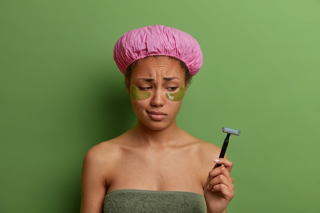 Sad dejected woman looks at razor, applies collagen patches, has eye skin rejuvenation treatment, wears bathing cap after taking shower, doesnt want to shave legs, isolated on green wall