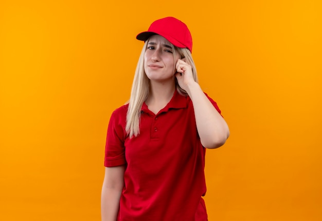 赤いtシャツとキャップを身に着けている悲しい配達の若い女の子は、孤立したオレンジ色の背景に頭に指を置きます