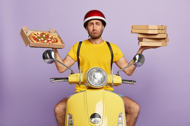 Sad deliveryman driving yellow scooter while holding pizza boxes