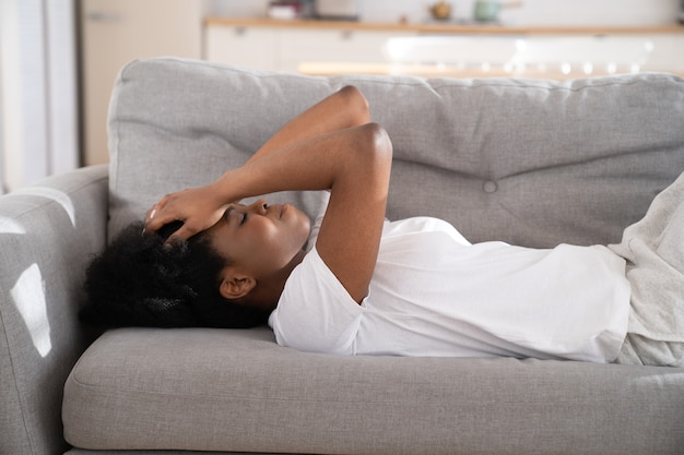 Sad depressed african woman lying on couch at home crying, feeling loneliness suffering from breakup