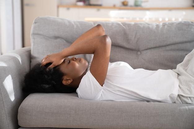 슬픈 우울 아프리카 여자 집에서 소파에 누워, 이별로 고통받는 외로움을 느끼고 울고