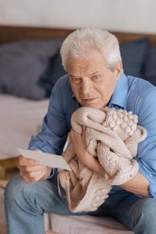 Грустный подавленный пожилой мужчина держит куртку жены и прижимает ее к сердцу, читая записку