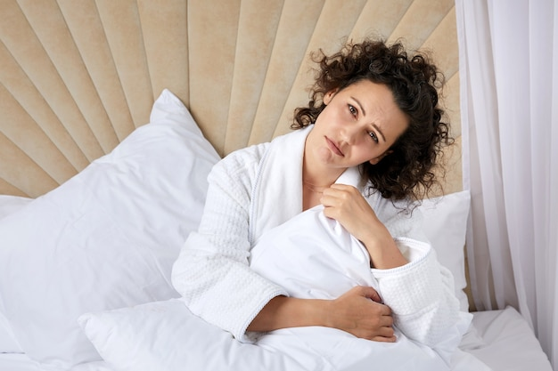 Sad depressed curly woman hugging pillow sitting in bed alone depression concept
