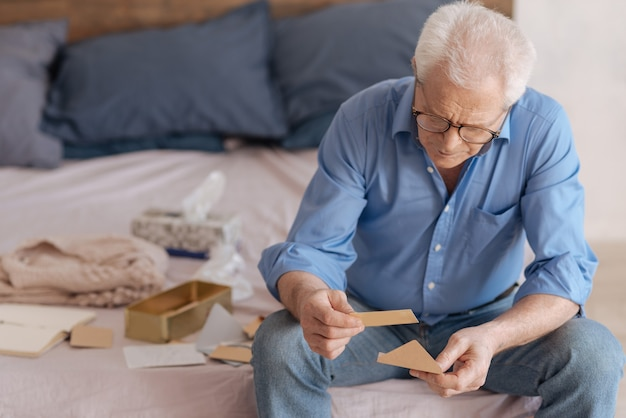 Sad depressed elderly men holding an envelope and reading an old note while thinking about his past