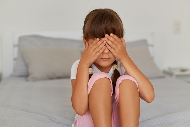Sad and depressed little girl wearing white t shirt and rose short sitting in bed crying, covering eyes with palms, feels sadness, posing alone in light room at home.