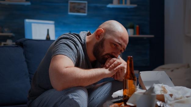 孤独を感じて泣いている悲しい落ち込んだ男慢性疲労は、移住に苦しんでいる疲れた病気の病気を動揺させます...