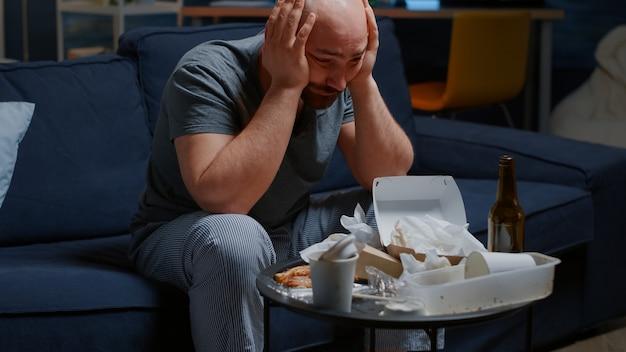 ソファに座っている悲しい落ち込んだ男は必死に孤独を疲れさせる