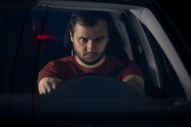Sad depressed man spending time alone at car at night feeling lonely