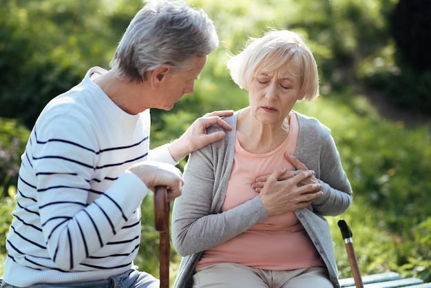 Грустная подавленная пожилая женщина трогает ее грудь и страдает сердечным приступом, в то время как ее престарелый муж беспокоится о ней и сидит на скамейке на открытом воздухе