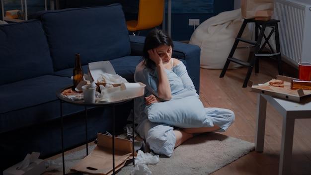 薄い床に座って孤独な絶望を感じている精神的な問題を抱えた悲しい落ち込んだストレスの犠牲者の女性...