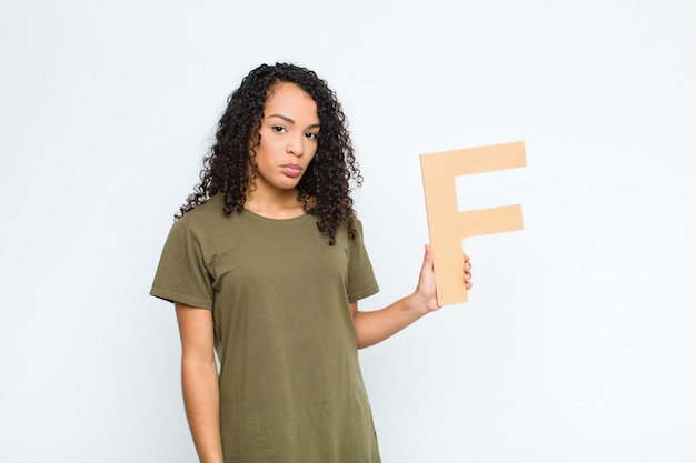 Sad, depressed, unhappy, holding the letter f of the alphabet to form a word or a sentence.