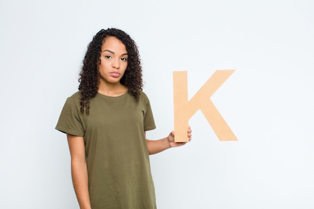 Sad, depressed, unhappy, holding the letter k of the alphabet to form a word or a sentence.