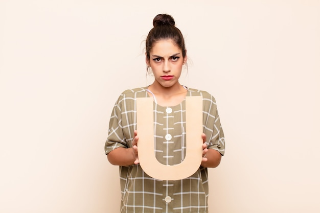 Sad, depressed, unhappy, holding the letter u of the alphabet to form a word or a sentence.