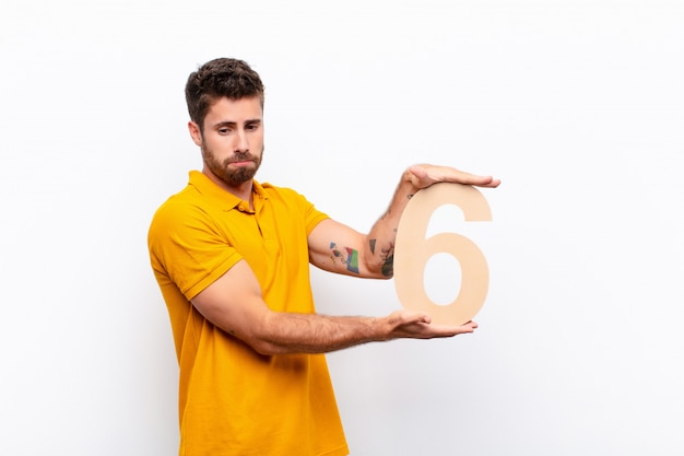 Sad, depressed, unhappy, holding a number 6.