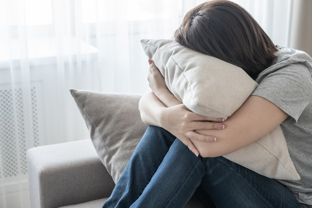 Sad depressed woman at home sitting on couch and hugging a pillow, loneliness and sadness concept
