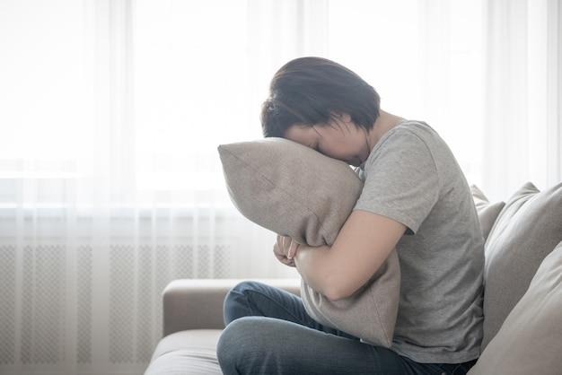 枕、孤独、悲しみの概念を抱いて悲しい落ち込んでいる女性