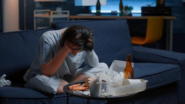 ソファに座って必死に揺れる悲しい落ち込んだ女性は孤独を疲れさせる
