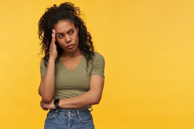 Sad depressed young woman in casual clothes touching her temple and looking away to the side at empty space isolated over yellow wall