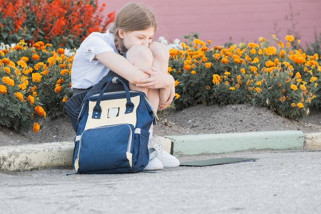 Sad desperate young girl suffering from bulling and harassment felling lonely, unhappy desperate and hopeless sitting outdoors. school isolation, abuse and bullying concept
