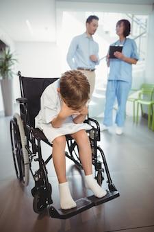 Sad disable boy in wheelchair in corridor