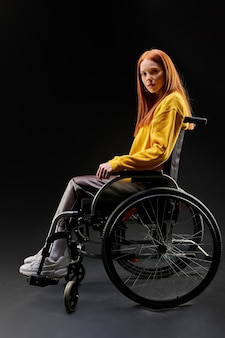 Sad disabled woman in a wheelchair, looking at camera depressed. redhead female in yellow casual shirt sits isolated on black background. health and people concept
