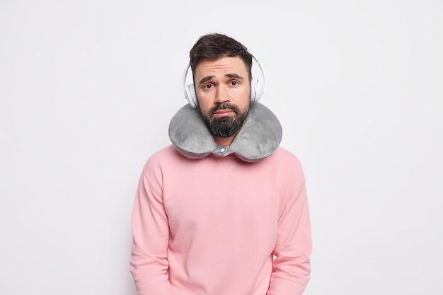 Грустный разочарованный европейский мужчина с густой бородой позирует с дорожной подушкой на шее, чтобы комфортно путешествовать, слушает музыку в беспроводных наушниках, одет в повседневную одежду
