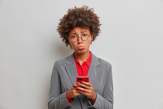 슬프고 실망한 여성 관리자 또는 비서가 직장에서 문제가 있고, 휴대폰을 사용하고, 중요한 전화를 기다리고, 어려운 상황을 해결할 수 없으며, 실내에 서 있습니다. 과학 기술