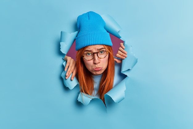 Sad disappointed redhead teenage girl purses lips and looks with sullen face expression wears blue hat and spectacles looks through hole of torn paper