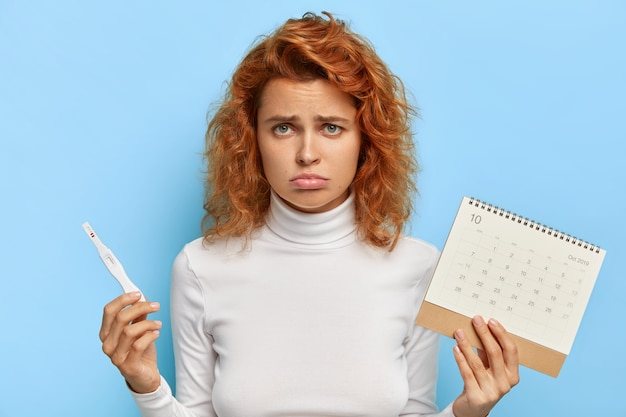 Sad disappointed redhead woman holds pregnancy test and menstruation calendar