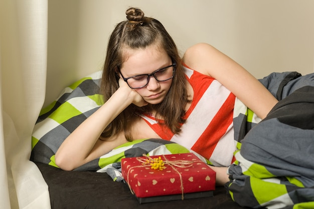 Sad disappointed teen girl looking at gift