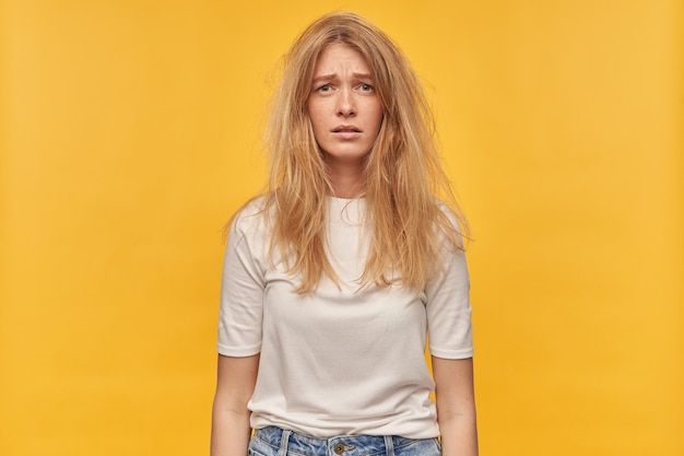 Sad disappointed woman with freckles and messy hair in white tshirt standing and feels depressed on yellow