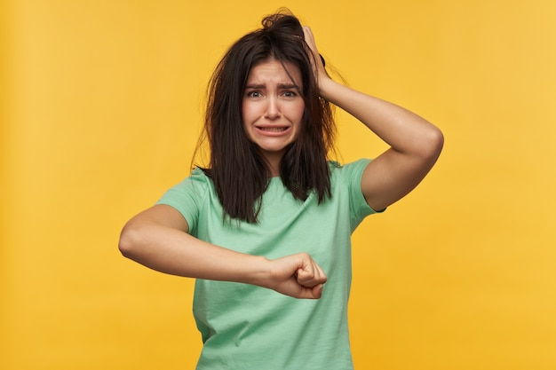Sad disappointed young woman with dark messy hair in mint tshirt keeps hands on head and late for a job isolated over yellow wall