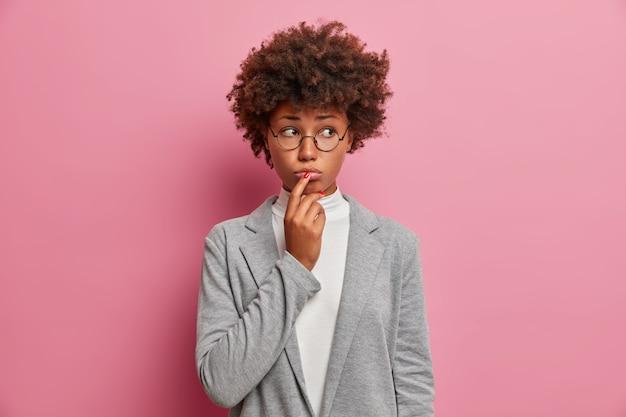슬픈 불만을 품은 곱슬 여성 임원 노동자는 불행하게 옆으로 쳐다보고, 입술을 꽉 쥐고, 후회를 표현하고, 문제가 있고, 좋은 조언이 필요하고, 정식으로 옷을 입는다.