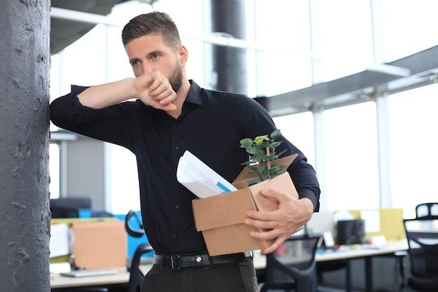 슬픈 해고된 직원이 사무실에서 사무용품을 가지고 가고 있습니다.