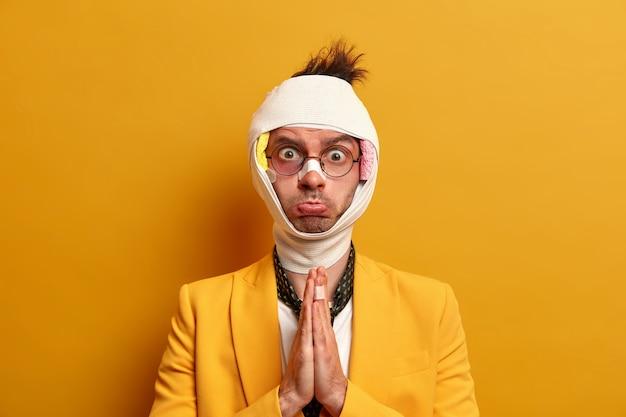 悲しい不機嫌な男は、手のひらを一緒に押し続けて助けを求め、頭に包帯を巻いて、鼻を骨折し、目の下に打撲傷を負い、黄色い壁に顔を腫れさせます。事故やけがの被害者