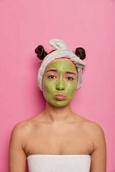 Sad displeased woman gets facial care having green mask on face