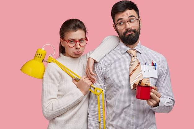 Triste dispiaciuti donna e uomo con gli occhiali, fanno il lavoro comune, tengono la lampada e la tazza di caffè, esprimono sentimenti negativi