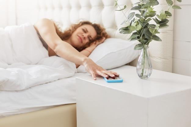 Грустная недовольная женщина просыпается рано утром, выключает будильник на смартфоне