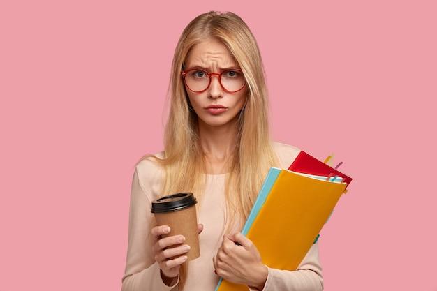 Грустная недовольная блондинка студентка колледжа позирует у розовой стены
