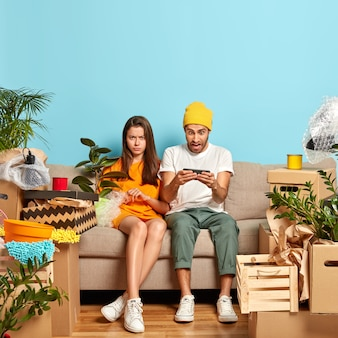 Sad dissatisfied girlfriend angry with boyfriend who obsessed with playing online game on smartphone, relocate in new just bought apartmet, have to unpack their belongings, sit on sofa in living room