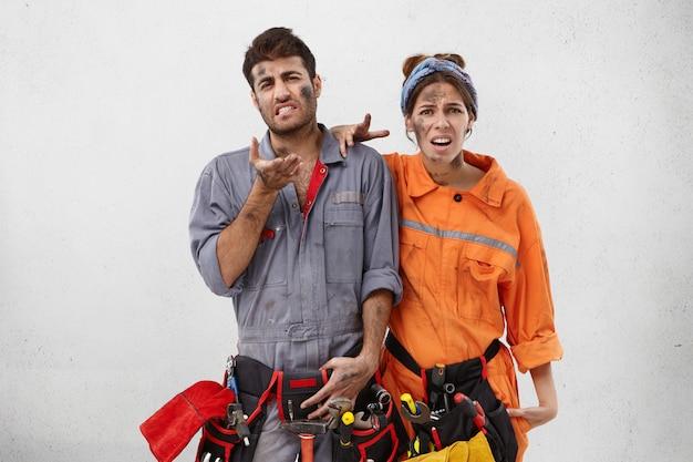 Печальный недовольный механик-мужчина и его хорошенькая жена, которая помогает мужу ремонтировать