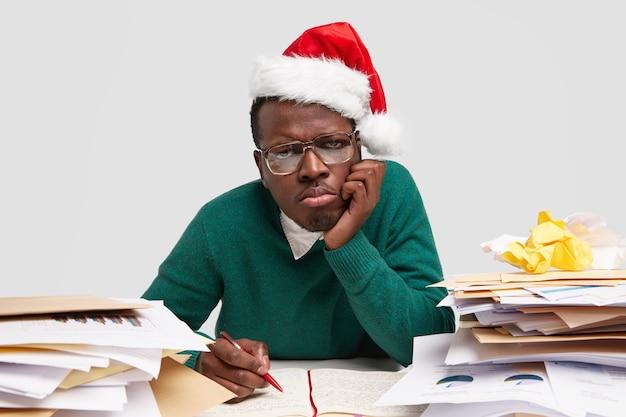 Sad dissatisfied man purses lips, keeps hand on cheek, wears santa claus hat, works hard before celebrating winter holidays