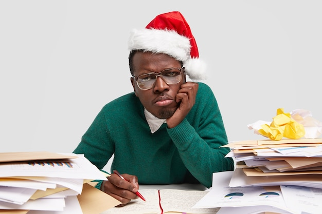 Грустный недовольный мужчина поджимает губы, держит руку на щеке, носит шляпу санта-клауса, много работает перед празднованием зимних праздников