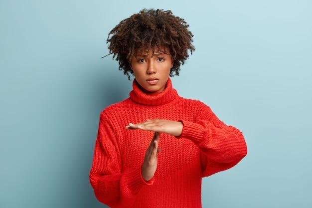 La donna frustrata e stanca triste insoddisfatta mostra il gesto di timeout, ha bisogno di fermarsi, chiede tempo per riposarsi dopo un duro lavoro, mostra il segno della mano di rottura, indossa un maglione rosso. concetto di linguaggio del corpo