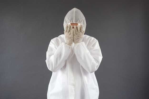 彼の顔を保持している防護服の悲しい医者