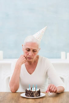 Sad elder woman looking at birthday cake with candle over table