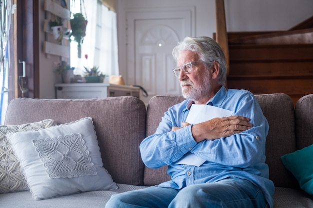 Sad elderly man reading health insurance deal closing looking and reading the medical results. sick mature senior hugging a sheet with the results or outcomes. checking health tests