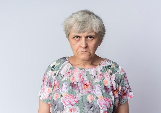 Грустная пожилая женщина смотрит изолированную на белой стене